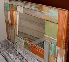 Scrappy-Chic Mirror made with pieces of wood scraps distressed with different colors or stains.