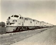 "Publicity photo of UP's ""Train of Tomorrow,"" which the railroad purchased in 1950 from GM. In this photo, the train appears to be running as eastbound no. 104, ""The City of Los Angeles,"" as evidenced by the train number displayed in the locomotive's number board. The train was comprised of an E7A diesel-electric locomotive and four Astra Dome cars: chair car, sleeper, diner, and observation-lounge."