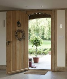 Gorgeous welcoming oak front door (love the potted topiary lollipop tree)