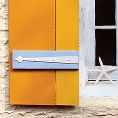 Orange-exterior-shutter - 20 Ways to Decorate with Orange and Yellow - Coastal Living