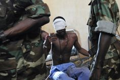 Sia Kambou—AFP/Getty Images March 29, 2013. Central African Seleka rebels speak to an injured Seleka rebel at a community hospital in Bangu...