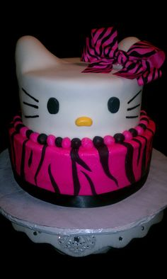 hello kitty cake!  hmm...cupcakes with jellybean nose, black licorice wiskers and chocolate kiss (pointy-side down in the white frosting) for eyes, fruit roll-up bow or some other candy bow...