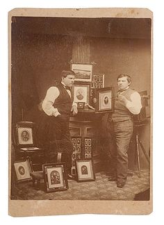 A fine cabinet card portrait of a photographer and his retoucher proudly displaying several examples of their work.  A wet-plate studio camera is visible in the right rear. With verso imprint M.J. Streuser, Photographer & Ferrotyper, Bellevue, Iowa.