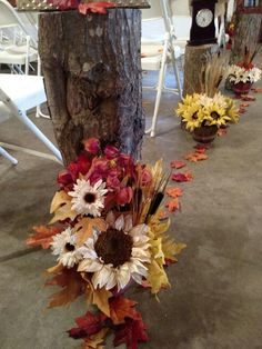 Tree stumps with fall flower for wedding aisle
