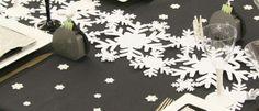 La nappe, d'un noir profond, met parfaitement en valeur la blancheur des différents flocons de neige présents sur la table.