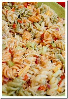 1 box Tri-Colored Rotini  {I use Barilla because I love the box!}  1 1/2 cups Italian Salad Dressing {I use Wish-Bone..I think it's the best!}  1/2 red onion, chopped  1 red bell pepper, chopped  1 green bell pepper, chopped  1 cup cheddar cheese, chopped  1/2 – 1 whole cucumber, peeled & chopped  1 tomato, chopped {optional}  Chopped black olives {optional}  1 tub shredded parmesan cheese