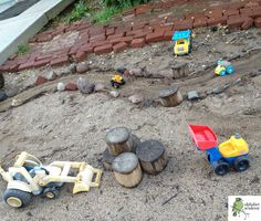 "A 'paved' road in a sandy area, outlined with small bits of rock, stone, brick & sticks. Construction trucks added - at Alphabet Academy North Preschool ("",)"