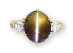 A CAT'S EYE ALEXANDRITE AND DIAMOND RING  Set with a cat's eye alexandrite weighing 10.02 carats, flanked on either side by an old mine-cut diamond, to the pavé-set diamond quarter-hoop, mounted in 18k gold.