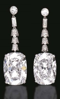 A MAGNIFICENT PAIR OF ART DECO DIAMOND EAR PENDANTS. Each set with a cushion-cut diamond, weighing approximately 23.11 and 23.49 carats, suspended by a series of single-cut diamond bell-shaped links and a baguette-cut diamond, from a diamond collet, mounted in platinum, circa 1925.
