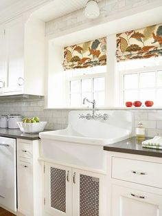 Love this big antique farmhouse sink, those gray counter tops with white cabinets, and that double window to look out!