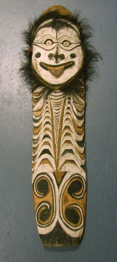 A Sepik River Ancestral hardwood shield finely incised and decorated with natural ochres and Cassowary feathers . H163cm