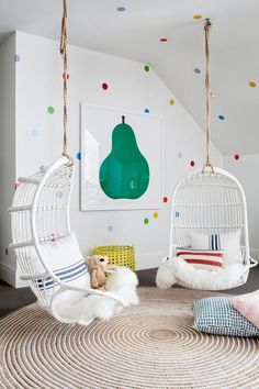 colorful polka dot wall decor, a bold fruit wall art and cool hanging chair make the nook super inviting