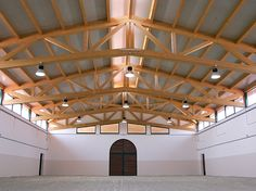 Internal riding arena with simple but elegant timber truss roof.    www.equidesign.it