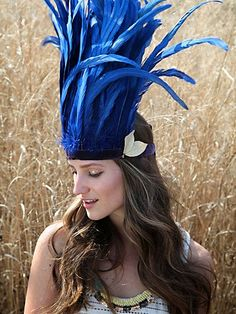 """From Freepeople's """"Festival"""" line. A fun piece that would definately keep you from getting lost for too long!   Wanderlust Feather Headdress $438     Blue-dyed tall feather headdress with purple velvet bottom ties and ivory leather leaf embellishment at bottom left corner. Take extreme head dressing to the next level with this all natural, statement-making piece."""