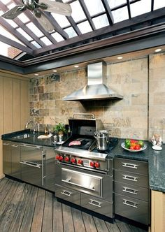 A former storage shed now houses an outdoor Wolf kitchen, Grill, side burners, hood, and a warming drawer.