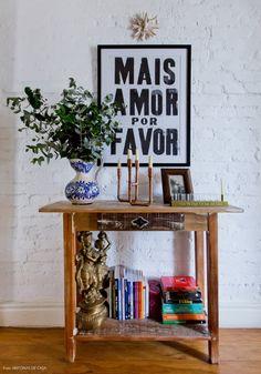 Hall para os quartos conta com parede de tijolinho pintada de branco e aparador…