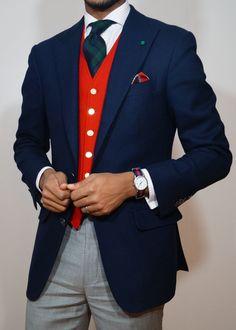 Shop this look on Lookastic: https://lookastic.com/men/looks/blazer-waistcoat-dress-shirt-dress-pants-tie-pocket-square-watch/13496 — White Check Dress Shirt — Dark Green Plaid Tie — Red Plaid Pocket Square — Red Waistcoat — Navy Wool Blazer — Red and Navy Horizontal Striped Watch — Grey Dress Pants