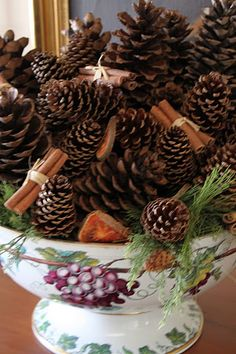 pinecones with cinnamon stick bundles and sprigs of cuts greenery around edge