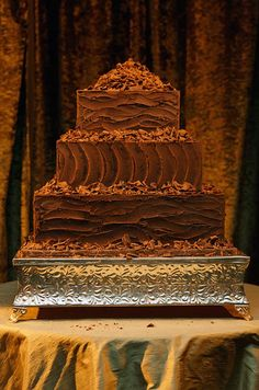 A rich chocolate groom's cake features piles of chocolate shavings and sculpted frosting on a simple square shape.