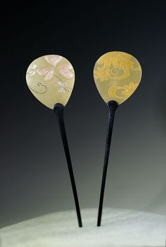 Japanese hairpins. Flattened celluloid hair pins in shape of fan and decorated with floral motifs.