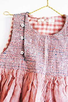 interesting use of narrow striped fabric, crushed and overstitched gathering forms the yoke...