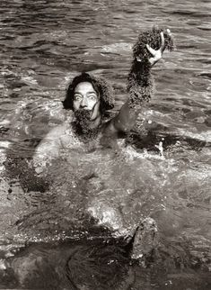 Salvador Dali swimming holding seaweed, and wearing seaweed beard and wig, 1955. (Photo by Hulton Archive)
