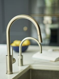 Modern integrated island sink with Quooker tap and marble effect countertops for dark grey-blue kitchen design.