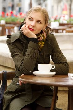 Image of 'Beautiful woman drinking coffee in outdoor cafe'