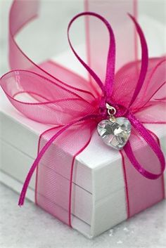 Make your package super feminine by adding a heart with a hot pink bow. #giftwrap #ribbon