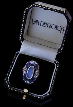 VAN DEN BOSCH Jewellery Rings/Earrings - BERNARD INSTONE (1891-1987) An Arts & Crafts silver and gold ring set with a central moonstone bordered with amethyst and pearls.  English. Circa 1930.
