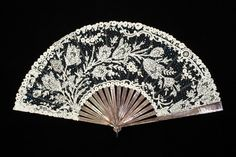 Lace fan  American, late 19th century  Leaf of black net applied with white Brussels lace and blue sequins, dark mother of pearl sticks and guards inset with sequins