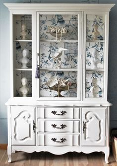 A beautiful vintage French Provincial China Cabinet that has been painted a creamy off white color. On the back wall is a beautiful paper which adds extra character. This piece is a sturdy solid wood construction with a lot of storage. Its a perfect addition to your Shabby