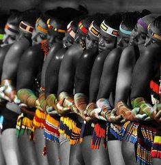 This picture features and represents people of Africa. They look to be in line doing some type of dance, dances are very common at African celebrations. The picture also the beads and bright colors used to dress them for their show.