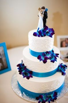 Our wedding cake with blue orchids. My mom painted the flowers on the cake topper to match the wedding flowers.: