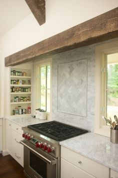 Farmhouse kitchen features cooking nook accented with rustic wood beam over ivory cabinets paired with white marble countertops and white marble backsplash flanked by built-in spice racks.
