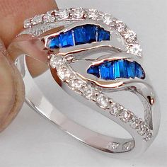 GENUINE BLUE SAPPHIRE TAPPER GEMSTONE WITH WHITE TOPAZ ACCENTS 925 STERLING SILVER RING SIZE 7 <br/><br/>Item Details: <br/>Metal: 925 Hallmarked Sterling Silver <br/>Stones: Blue Sapphires Tapper <br/>Accent Stones: White Topaz <br/>Stone Weight: 3.52 Cts <br/>Approximate Ring Head Size: 10x20mm <br/>Approximate Ring Weight: 3.07g <br/><br/>WHITE TOPAZ <br/>Pure topaz is colorless and transparent but is usually tinted by impurities