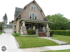 Gambrel roof home built in 1917 at 123 W End St in Alma, MI. Asking price $144,900. The 3 story home features 2,912 sq ft, 6 bedrooms, 2 bathrooms, stone exterior, built-in bookcase, foyer, formal dining room, den/study, fireplace, hardwood floors, beamed ceilings, original woodwork, beveled glass pocket doors, double-decker glass enclosed porches overlooking backyard, large updated kitchen with island, 3 bedrooms and 10 x 16 bonus room on 3rd floor, detached garage and 6,970 sq ft lot.