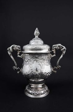 THE LOUTH HUNT CUP A large Irish silver two handled cup and cover, in Georgian style, Dublin 1913, mark of West & Son, with fruiting vine finial, domed cover, the ogee body embossed with scrolls and fruit, the handles wrapped with dolphins, on a spreading foot, the cartouches inscribed ''Louth Hunt 1922'', and ''Won by the Ward'' (c.90ozs). 40cm high