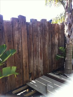 Garden fence reclaimed railway sleepers - would make an interesting backdrop to a jungle style garden, add some chunky rope between bollards & an Indiana jones type theme