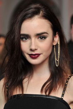 Lily Collins' gorgeous gold piece pulls her textured hair, beautiful burgundy lips, and the gold rock studs on her dress together for a sophisticated yet unique look!
