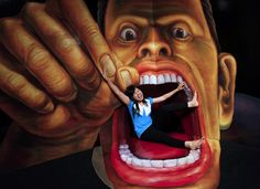A visitor poses with a 3D art work during a Japanese Trick Art exhibition at a