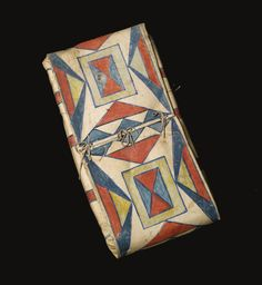 TWO CROW PAINTED PARFLECHE CONTAINERS one, a bonnet case, of cylindrical form, painted with a central diamond motif, flanked at each end with narrow strips enclosing triangles, trimmed with a long, fringed panel, the other, an envelope, with a pair of concentric rectangles enclosing hourglass designs.