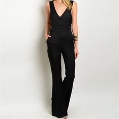 "Hot Black Jumpsuit This chic jumpsuit features exposed sides, v-neckline and a deep v-shaped back. Has hidden pockets and flared pant legs. Lace bandeau pictured underneath NOT included. Small measures 13.5"" across when laying flat and 59.5"" long. Runs small. Pants Jumpsuits & Rompers"