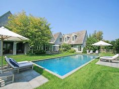 I LOVE HOW THIS HAMPTONS POOL AREA IS FILLED WITH GRASS AND NOT TILE