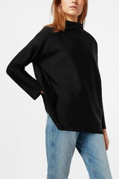 The Beijing Turtleneck combines a lux feel of a shiny material with a clean-cut silhouette. It has a mock turtleneck, dropped shoulders and raw cut edges.