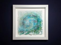 Title: Wild One (2017) Of the Rock and Sea, Hawaii inspired series, at maywaynorth.com Description ~ In cascading colors of blue greens, white, and tones of volcanic rock all inspired by Oahus 7 mile North Shore surf. Glass is fused with sea glass. Organic edges and silver leaf throughout the form enhance the gorgeously wild and rough texture. Kiln and/ or flame fused. NO resins or glues that will yellow. Details ~ The 7 sculpture is free form square and framed behind glass in a 10 s...