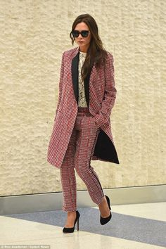 A new look: Victoria Beckham swapped her signature style for a trouser suit on Sunday when...