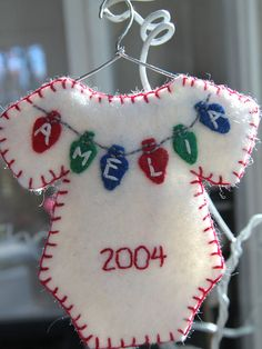 Adorable baby onesie ornament handcut and handstitched with babys name spelled out on Christmas lights measuring just 1/2 inch (1.3cm). On the ornament pictured, I have also stitched the childs year of birth. I could also use the full date (e.g. 11-04-11)    The ornament is made of quality wool blend felt and filled with felt scraps for weight and firmness. It hangs on a tiny handmade hanger made from a paper clip.    Colors for this ornament are traditional Christmas colors including re...