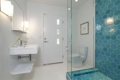 """The architect designed the vanity for the first-floor bathroom, which opens to both the media room and the backyard. Though he went with """"seconds"""" tile elsewhere, for this bathroom Popp sprung for the hexagonal blue tiles from the latest collection by <a Heath Tile, Shower Floor, Shower Tiles, Shower Pan, Hexagon Pattern, Hexagon Tiles, Blue Tiles, Tile Installation, Architect Design"""