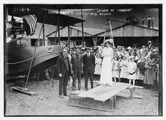 """As per Glenn Curtiss - Pioneer of Flight (1991), by Cecil R. Roseberry, this photo depicts the christening and launching of the Curtiss Model H Flying Boat """"America"""" on June 22, 1914 in Hammondsport, New York, just adjacent to Keuka Lake. From left to right, aviators John Cyril Porte, George E.A. Hallett, and (builder) Glenn Curtiss stand below 16-year old Miss Katherine Masson. Miss Masson, the daughter of Leon Masson, an official with the Pleasant Valley Wine Company"""